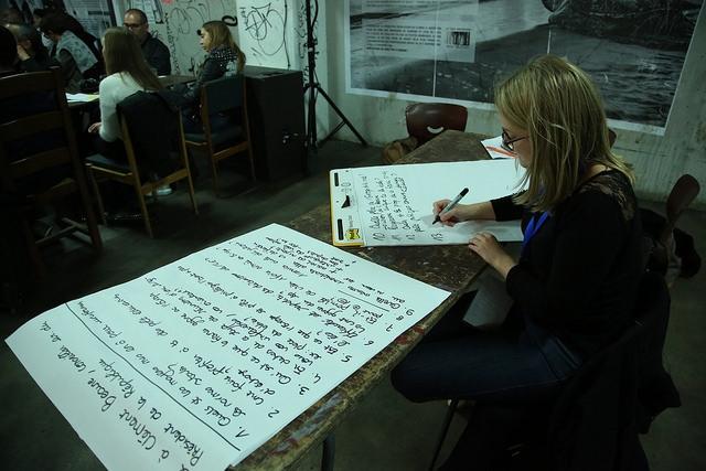 Une organisatrice écrit des questions formulées par le panel