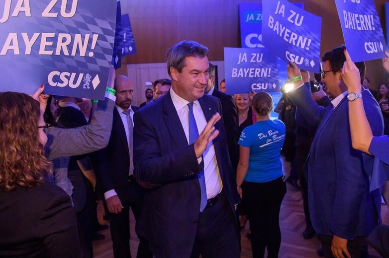 Markus Söder, chef de file de la CSU, entouré de militants affichant le slogan du parti :