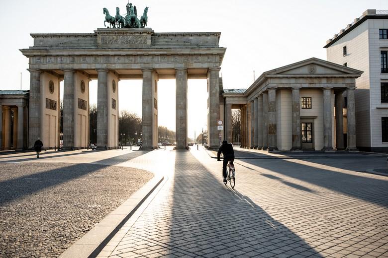 Un cycliste passant sur la Pariser Platz déserte, au pied de la porte de Brandebourg, à Berlin - Crédits : Alvarez / iStock