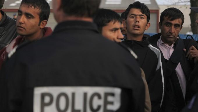 Des officiers de police expulsent des migrants du camps de Calais Schengen immigration quotas asile