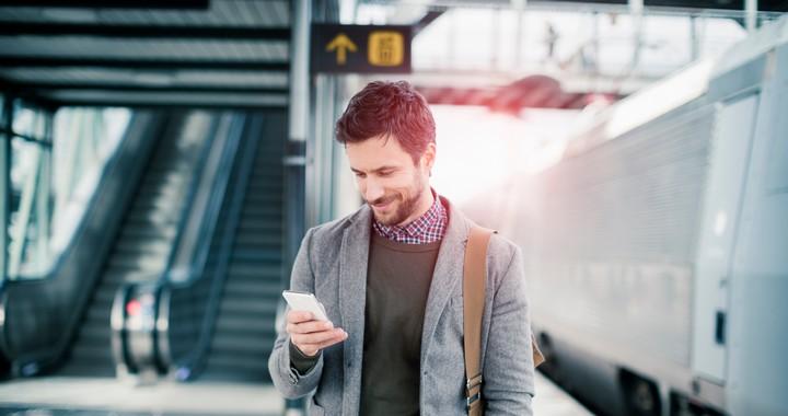Un homme utilisant un smartphone dans une gare