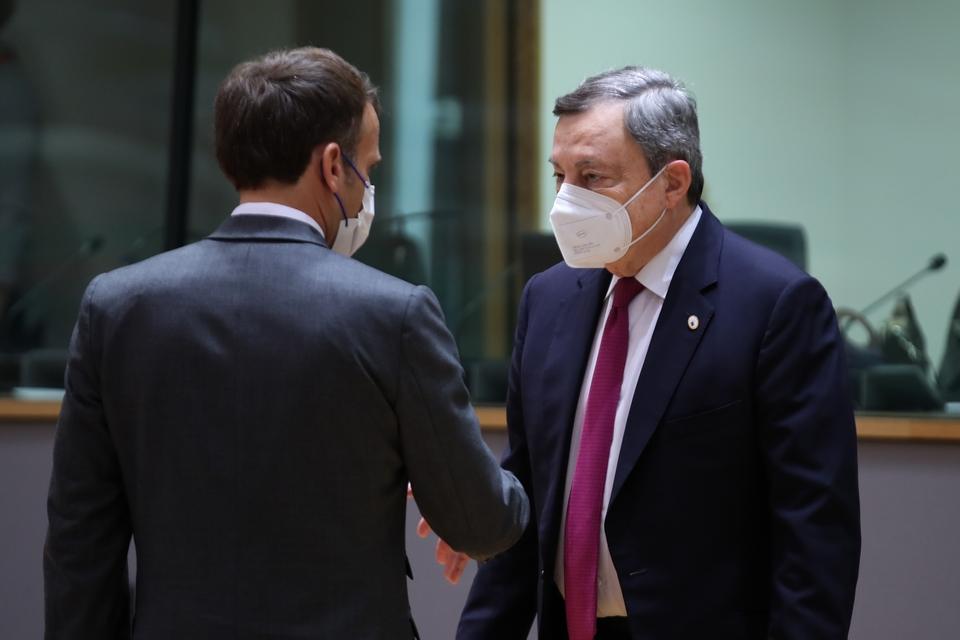 Le président du Conseil italien Mario Draghi (à gauche) regarde les mesures impulsées par son homologue de l'autre côté des Alpes
